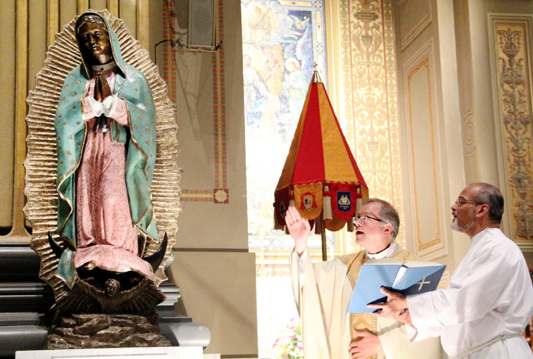 Fr. Denis Gill blesses the new bronze statue of Our Lady of Guadalupe which stands behind the altar rail in the left transept of the Cathedral Basilica of SS. Peter and Paul in Philadelphia.
