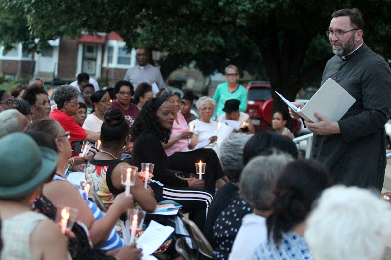 Fr Christopher Walsh, pastor of St Raymond, leads the prayer service out front of St Raymond at dusk