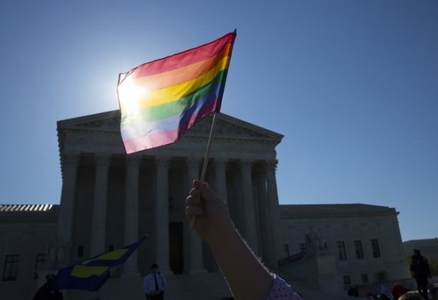 A supporter for same-sex marriage stands outside the U.S. Supreme Court on April 28 in Washington. (CNS/Tyler Orsburn)