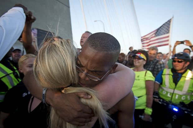 People hug as they gather on the Arthur Ravenel Jr. Bridge in Charleston, S.C., June 21. Thousands gathered on the bridge to show solidarity after nine African-Americans were shot to death by a young white man the evening of June 17 at the city's Emanuel African Methodist Episcopal Church. (CNS photo/Carlo Allegri)