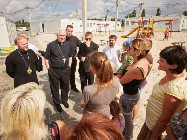 Ukrainian Catholic Bishop Vasyl Tuchapets of Kharkiv, Archbishop Joseph E. Kurtz of Louisville, Ky., president of the U.S. Conference of Catholic Bishops, and Father Serhiy Koval, director of the local Caritas organization, speak to internally displaced Ukrainians at a modular camp in Kharkiv, June 21. (CNS photo/Sergey Kozlov, EPA)
