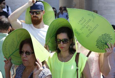 Tourists shield themselves from the sun with leaf-shaped posters received from environmental activists in St. Peter's Square at the Vatican June 28. Some 1,500 people marched to the Vatican in support of Pope Francis' recent encyclical on the environment. (CNS photo/Paul Haring)