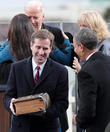 Beau Biden, son of U.S. Vice President Joe Biden, carries the family Bible as he walks past President Barack Obama after the vice presidential swearing-in on Inauguration Day on the West Front of the U.S. Capitol in Washington in this 2013 file photo. (CNS photo/Win McNamee, pool via Reuters)