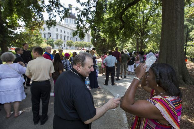 Bishop Robert E. Guglielmone of Charleston, S.C., talks to Barbara Thompson of  Manning, S.C., while she waits in the heat outside the South Carolina Statehouse in Columbia June 24. Inside the Capitol the body of the Rev. Clementa C. Pinckney, a pastor and state senator, lay in state. The pastor of Emanuel African Methodist Episcopal Church in Charleston was one of nine people shot and killed at the church June 17. (CNS photo/Mic Smith, The Catholic Miscellany)