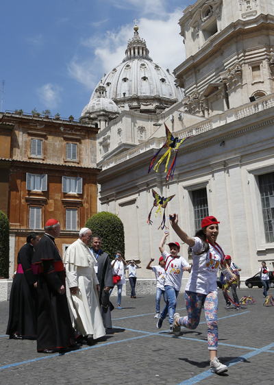 Pope Francis watches as children of Italian prisoners fly kites before their audience with the pope in Paul VI hall at the Vatican May 30. (CNS photo/Paul Haring)