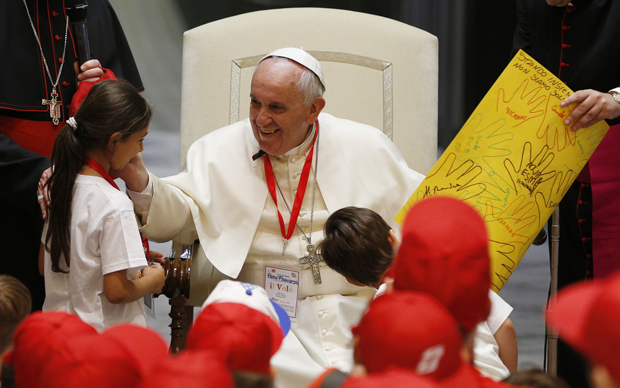 Pope Francis greets a girl after accepting a gift from her during a meeting with children of Italian prisoners in Paul VI hall at the Vatican May 30. (CNS photo/Paul Haring)
