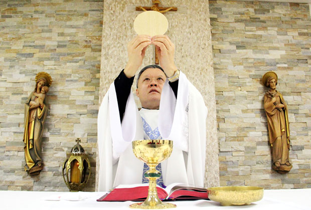 Msgr. Joseph Trinh, pastor of St. Helena Parish in Philadelphia, consecrates the Eucharist at Mass. (Sarah Webb)