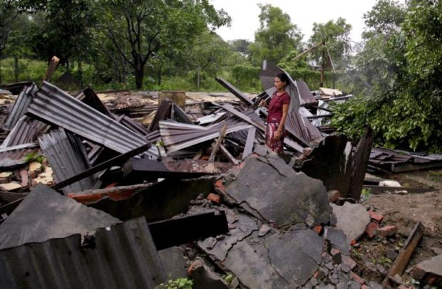 A woman stands among the rubble of a destroyed building hit by tornado in Sittwe, Myanmar, July 27. Aid groups say the military's blocking of relief supplies to displaced Kachin civilians violates international humanitarian law. (CNS photo/Nyunt Win, EPA)