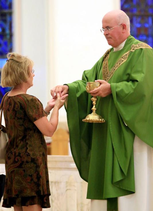 pastor Fr Ed Brady distributes communion
