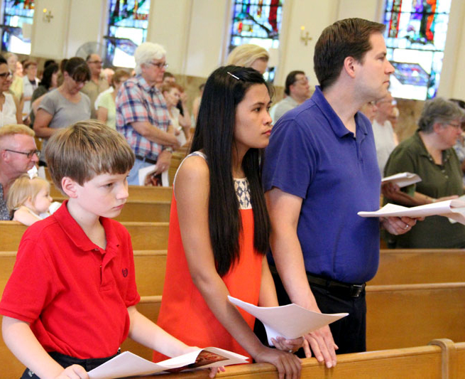 David Gosik prays along with his step-mother Kimberly and father Kevin