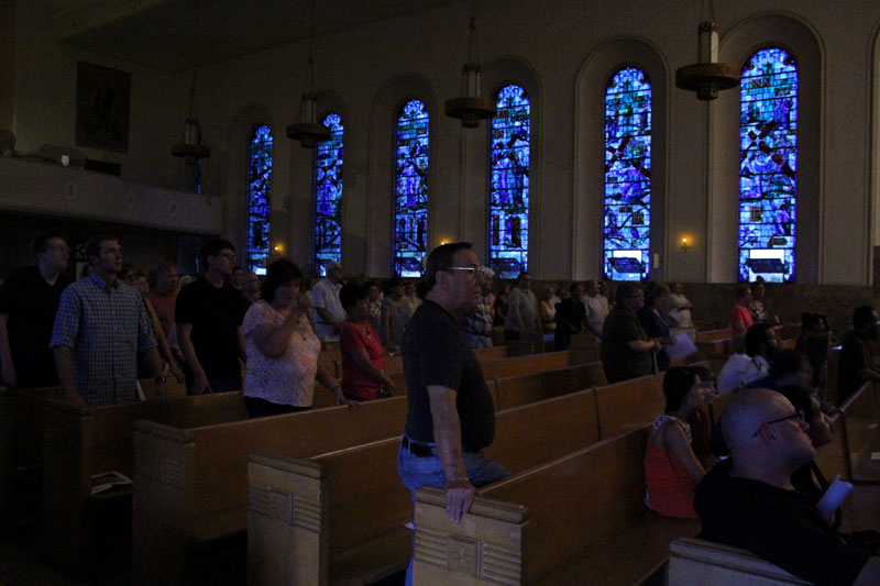 The lights are turned out for exposition, the church is illuminated by the beautiful stain glass windows