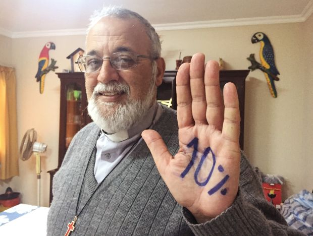 """Camillian Father Mateo Bautista Garcia shows his hand with """"10%"""" written on it. The priest wants Bolivia's government to spend 10 percent of its budget on health care. (CNS photo/David Agren)"""
