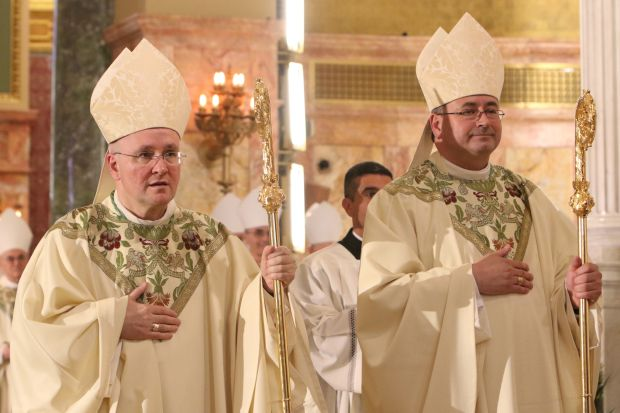 Auxiliary Bishops James Massa, left, and Witold Mroziewski of Brooklyn, N.Y., hold their pastoral staffs during their episcopal ordination July 20 at the Co-Cathedral of St. Joseph in the Prospect Heights neighborhood of Brooklyn. Bishop Massa, 54, was born in Jersey City, N.J., while Bishop Mroziewski is a native of Augustow, Poland. (CNS photo/Gregory A. Shemitz)