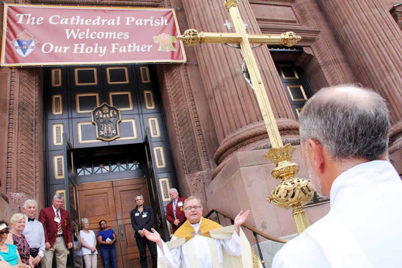 Father Dennis Gill, rector of the Cathedral of SS. Peter and Paul, leads prayers at the unveiling of a large banner welcoming Pope Francis, and the thousands of visitors coming to Philadelphia, Sept. 26-27. (Sarah Webb)