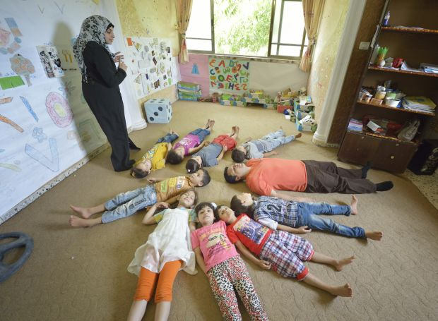 A woman leads a relaxation activity for children in Beit Hanoun, Gaza Strip, June 7. The program, designed to help children deal better with trauma and stress, is supported by Caritas Internationalis. (CNS photo/Paul Jeffrey)