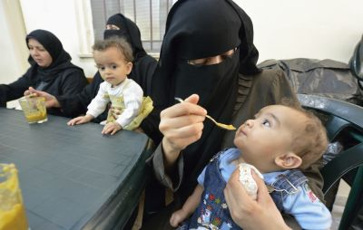 A mother feeds her child in a feeding program clinic in Gaza City. (CNS photo/Paul Jeffrey)