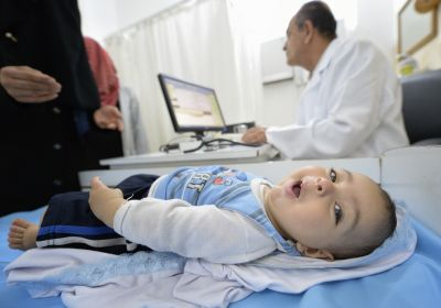 A baby looks around while the mother talks to a doctor in Gaza City, June 6. The clinic serves Palestinian refugees and is supported by the Pontifical Mission for Palestine and the Catholic Near East Welfare Association. (CNS photo/Paul Jeffrey)