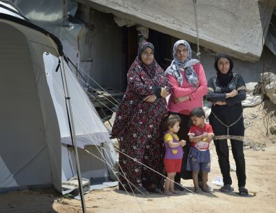 Women and children stand beside their tent and in front of the rubble of their home in Gaza City June 4. Houses in the area were destroyed during the 2014 war between Israel and the Hamas government of Gaza. (CNS photo/Paul Jeffrey)