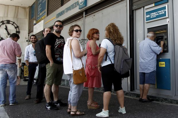 People queue to withdraw money from an ATM outside a branch of Greece's National Bank in Athens, Greece, July 6. (CNS photo/Alexandros Vlachos, EPA)