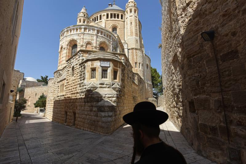 An Ultra-Orthodox Jew walks past the Dormition Abbey on Mt. Zion in Jerusalem July 27. Christian leaders want Israel to step up protection of Christian sites. (CNS photo/Debbie Hill)