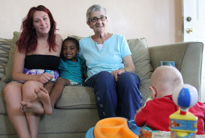 Cecilia Paul, center, enjoys the closeness of family in her home, with daughter Taylor (left) and son Jamil, both of whom she cared for as a foster mother before adopting them. Also brightening the home is her newest charge, an infant boy (lower right). (Sarah Webb)