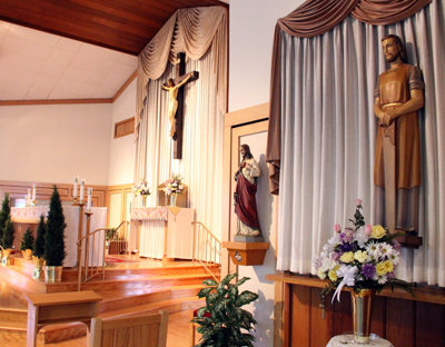 The sanctuary of the closed St. Joseph the Worker Church features a statue of St. Joseph holding a saw, at right. (Sarah Webb)