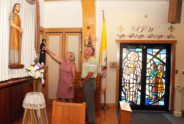 Rick and Carol Trailes view a statue of St. Joseph the Worker in his namesake church during an open house July 26. The church closed June 30, and a portion of its property is slated to be sold. (Sarah Webb)