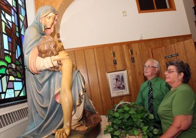 Ben and Linda Minnes, who were married in St. Joseph Church in 1968, view a statue in the now-closed church July 26 during a final open house before the property is sold. (Sarah Webb)