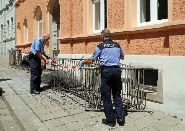 Two police officers set up a barrier in front of a building June 28 after a fire destroyed a reception center for asylum seekers in Meissen, Germany.  (CNS photo/Roland Halkasch, EPA)