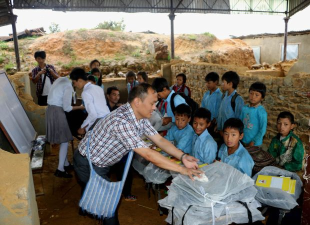 Salesian Father Savio Rai helps distribute school materials to students in a government-run school in Chaghare, Nepal, July 9. The school was damaged in the April 25 earthquake, which destroyed more than 25,000 classrooms in nearly 8,000 schools. (CNS photo/Anto Akkara)