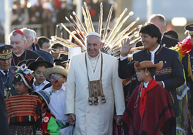 Pope Francis walks with Bolivian President Evo Morales and a children in traditional dress as he arrives at El Alto International Airport in La Paz, Bolivia, July 8. The airport is at 13,325 feet above sea level. (CNS photo/Paul Haring)