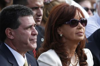 Paraguay's President Horacio Cartes and Argentina's President Cristina Fernandez de Kirchner wait for Pope Francis' arrival to celebrate Mass in Nu Guazu Park in Asuncion, Paraguay, July 12. (CNS photo/Paul Haring)