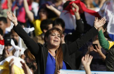 A woman raises her hands as people celebrate before Pope Francis' arrival to celebrate Mass in Nu Guazu Park in Asuncion, Paraguay, July 12. (CNS photo/Paul Haring) See POPE-NUGUAZU July 12, 2015.