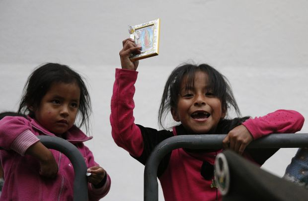 A young girl holds an image of Our Lady of Guadalupe as she waits for Pope Francis' arrival for a meeting with representatives of civil society in the Church of St. Francis in Quito, Ecuador, July 7. (CNS photo/Paul Haring)