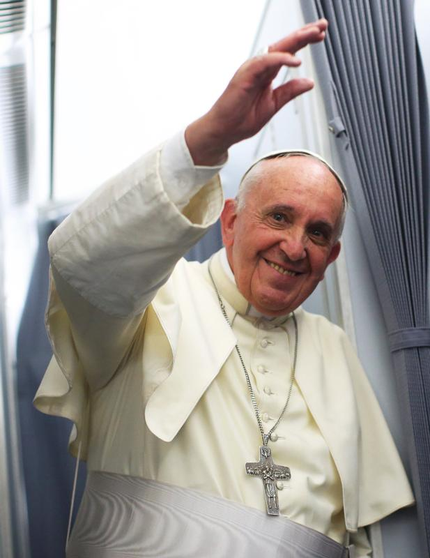 Pope Francis smiles on board papal plane during his return to Rome from Asuncion, Paraguay, July 12. New Gallup poll shows pope's favorability has dropped among Americans. (CNS photo/Alessandro Bianchi, Reuters)