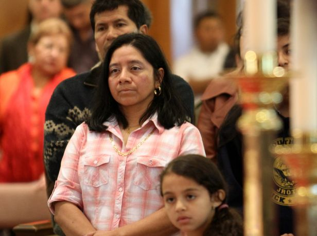 Hispanic worshippers stand during a special Mass honoring immigrants at St. John the Evangelist Church in Riverhead, N.Y., Oct. 30, 2011. (CNS photo/Gregory A. Shemitz, Long Island Catholic)