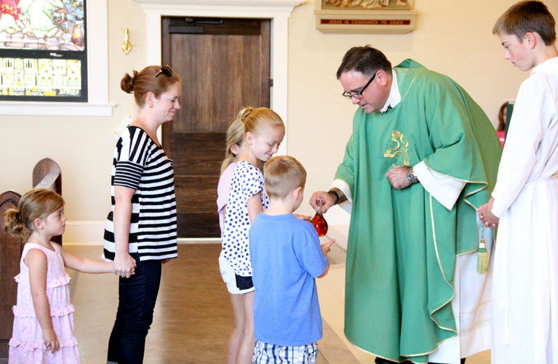 The Brookreson Family bring up the gifts to Fr. Joseph C. Bordonaro (server Matthew Quigley)