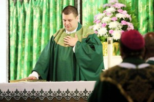 Fr Tom places his hands on the Book of the Gospels and recites the Oath of Fidelity