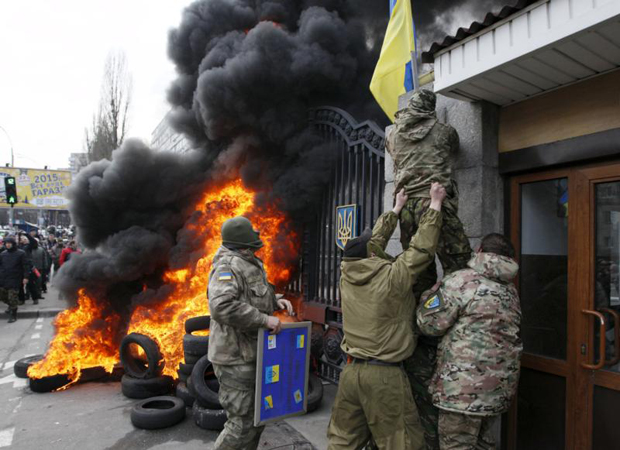 Servicemen from the Aydar battalion throw a Ukrainian flag from the building of Ukraine's Defense Ministry in Kiev during a protest against the disbanding of the battalion in this Feb. 2 file photo. (CNS photo/Valentyn Ogirenko, Reuters)