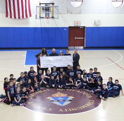 Visitation Community Center celebrates the check presentation in the frequently used gymnasium. (Sarah Webb)