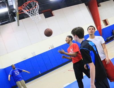 Boys play basketball under the watchful eye of a volunteer Visitation coach. (Sarah Webb)