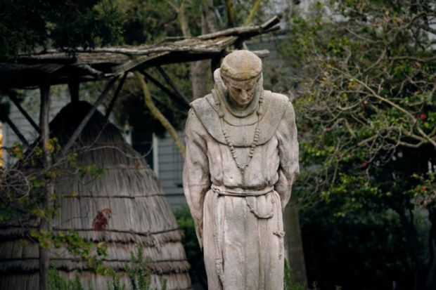A stone statue of Blessed Junipero Serra by artist Arthur Putnam is seen in the cemetery and garden at Mission San Francisco de Asís, also known as Old Mission Dolores, in San Francisco. In the back is an Ohlone ruway, a traditional California coastal native house made of tule. (CNS photo/Nancy Wiechec)