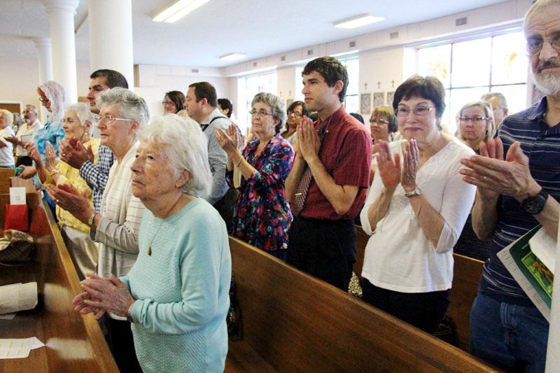 the congregation applauds the newly installed Fr. Jason Kulczynski