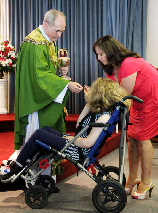 Fr. Jason Kulczynski gives communion to Danielle DeCarlo and her mother Mary Jean