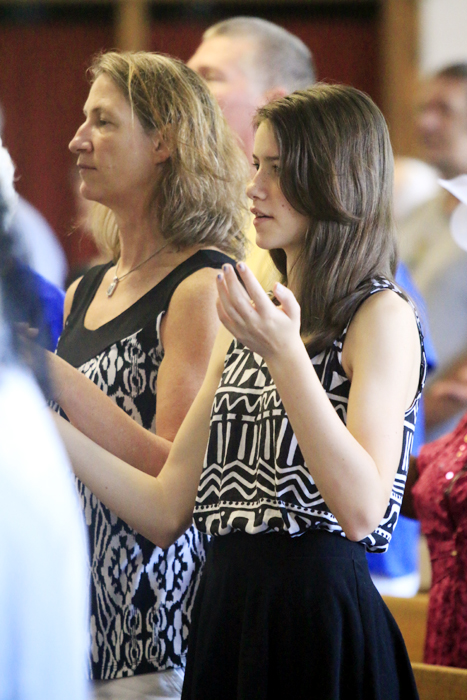 Jody Sweeney and her daughter Mary hold hands as they pray