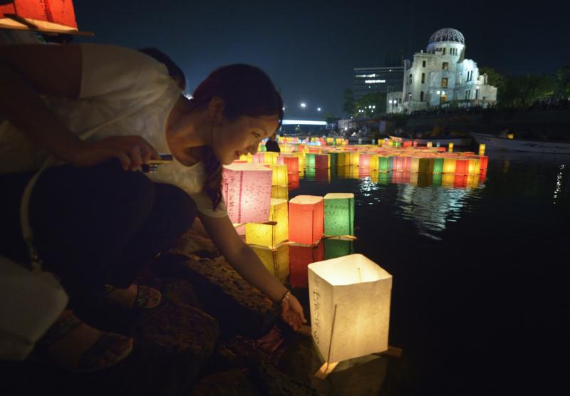 A woman sets a floating candle lantern on the river Aug. 6 in Hiroshima, Japan. The lanterns, thousands of which were launched on the 70th anniversary of the atomic bombing of the city, bear handmade messages and drawings, conveying each person's prayers for peace and comfort for the victims of the violence. In the background are the ruins of a building damaged by the bomb and now converted into a peace memorial. (CNS photo/Paul Jeffrey)
