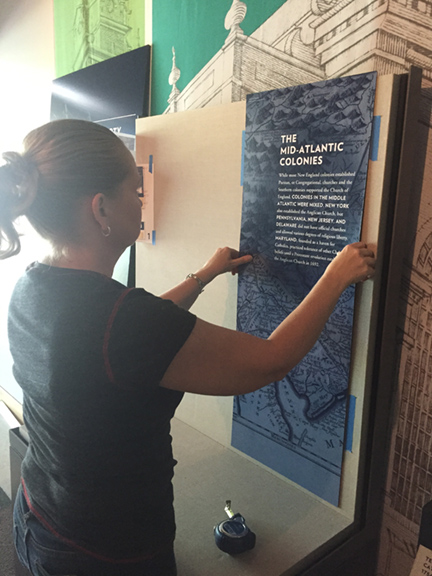 A staffer with the National Constitution Center in Philadelphia sets up an exhibit charting the growth of religious liberty in the United States.