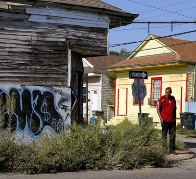A man walks past an abandoned building in the Upper Ninth Ward neighborhood of New Orleans Aug. 1. (CNS photo/Jonathan Bachman, Reuters)