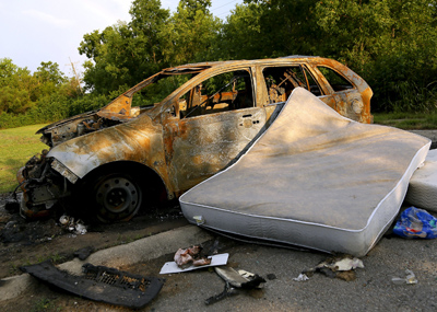 An abandoned car is seen in the Lower Ninth Ward neighborhood of New Orleans July 31. (CNS photo/Jonathan Bachman, Reuters)