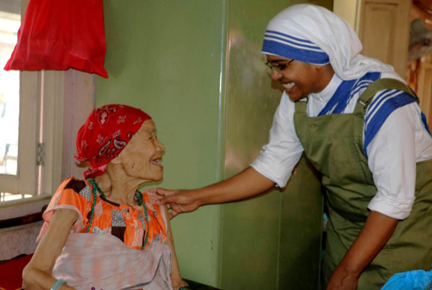 A woman smiles as she is greeted by Sister Marica of the Missionaries of Charity at a home for the elderly in the Pashupatinath temple in Kathmandu, Nepal, July 4.  The nuns have been caring for the dying and the elderly sick at the destitute center since 1978, when Mother Teresa initiated the service at the Nepal's holiest Hindu temple. (CNS photo/Anto Akkara)